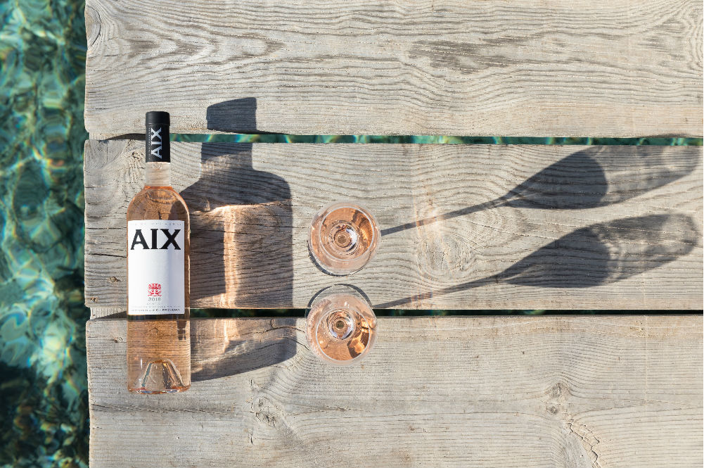 Aix rosé bottle adjacent to two glasses, all on wooden dock with clear sea underneath in background