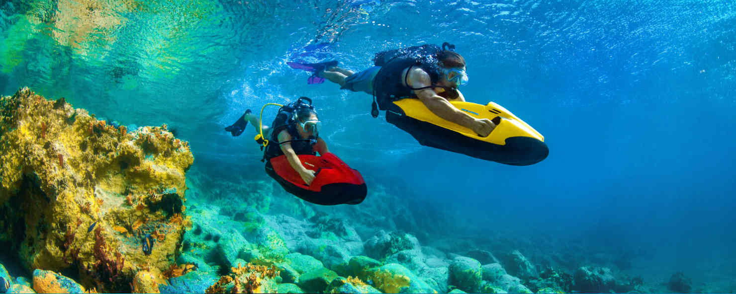 2 people using Seabobs underwater, passing vibrant coral