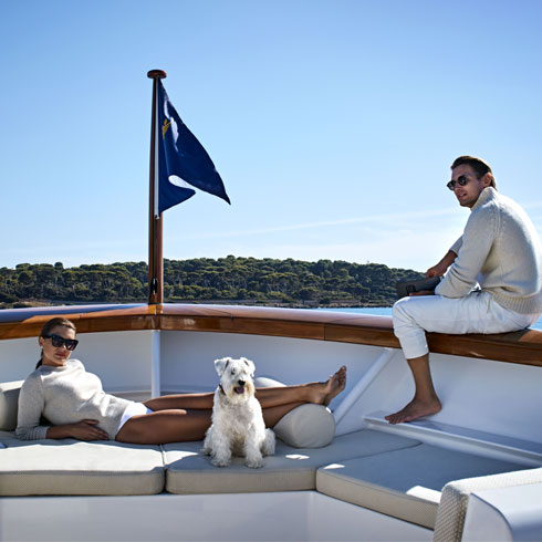 A young couple and their dog relaxing on their yacht.