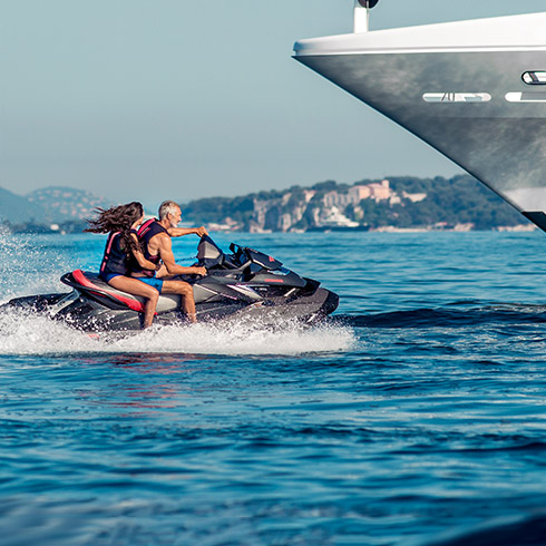 2 people enjoying a jet-ski by the side of their yacht.