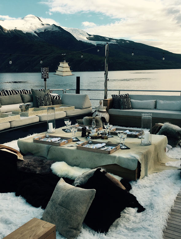 Decking shot of alfresco dining with fur rugs and cushions