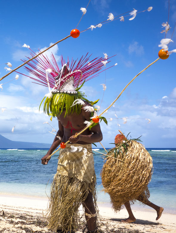 Namba tribesmen on the beach with head dress and grass skirts