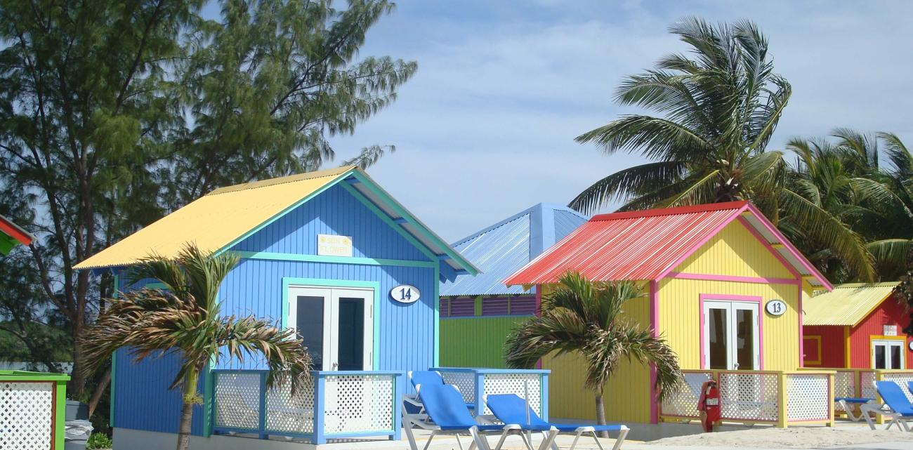 Colourful, beachside houses nestle amidst swaying palms