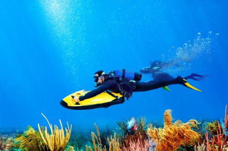 Two divers using Seabobs to dive across a beautiful marine landscape
