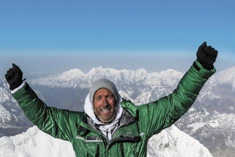 Ben Fogle in a green coat, grey hat, cheering on top of a snowy mountain