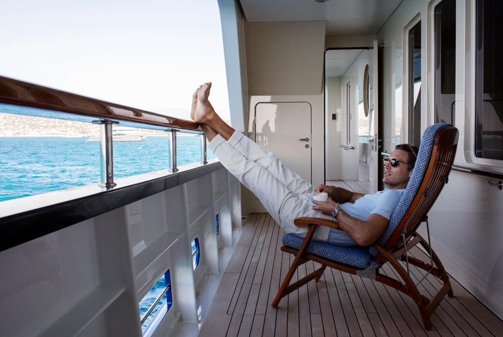 A man relaxing on the deck of a superyacht