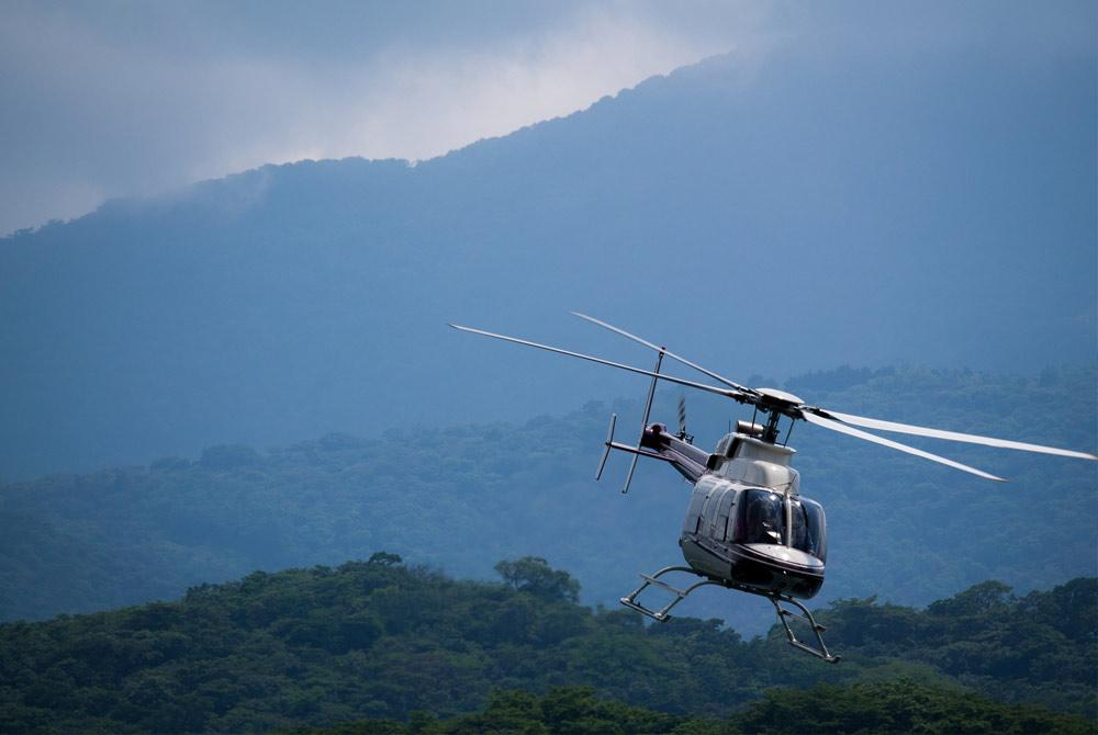 helicopter flying over lush hills